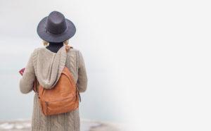 Figura femenina con mochila y sombrero de espaldas