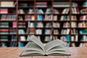 Fotografía de un libro abierto en la mesa de una biblioteca